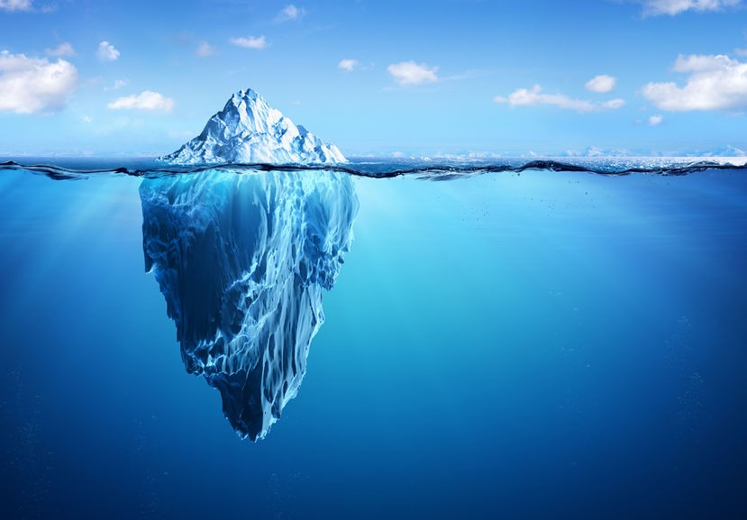 Photo of a floating iceberg, with the small white tip above the surface against the sky and the majority of it visible below