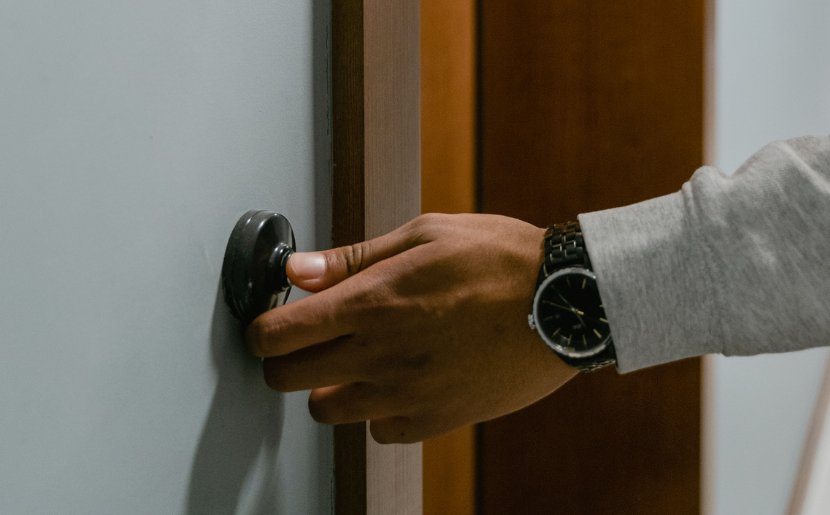 A person rings a doorbell.