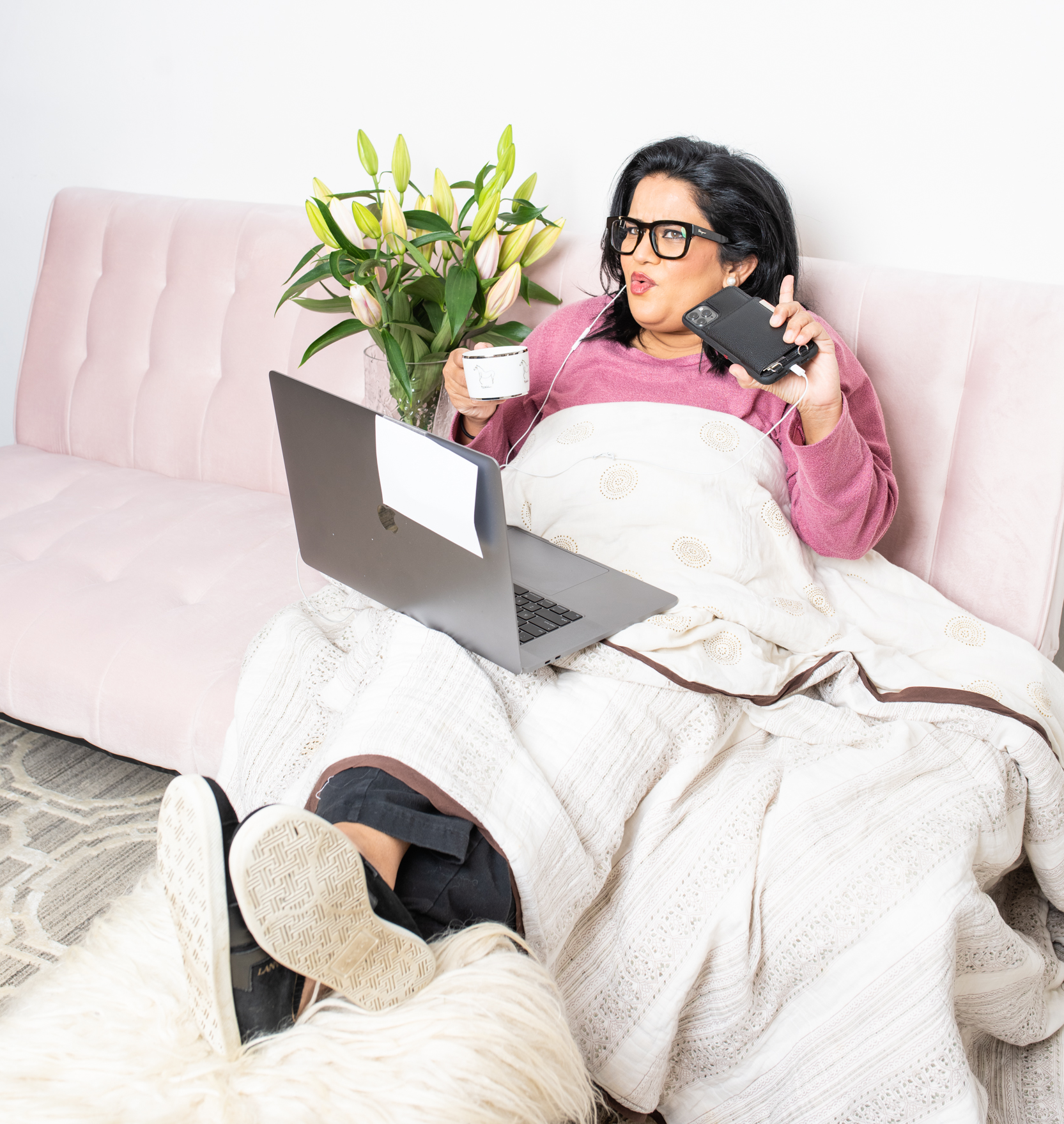 A comedian sits on a couch with a laptop, coffee, and phone. She may or may not be working.