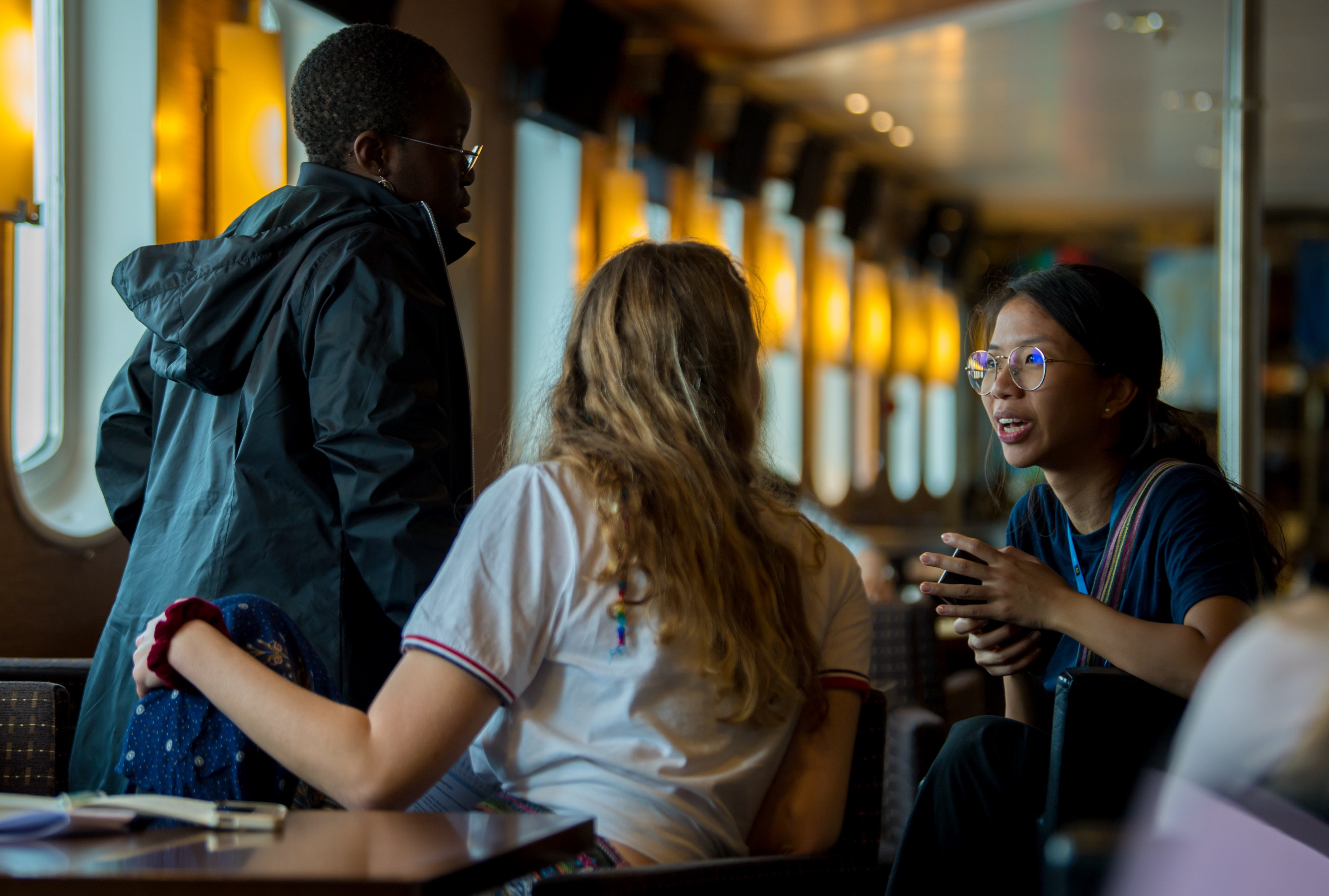 UT student Seyi Odufuye talks with other ClimateForce students on the ship during their trip to the Arctic.
