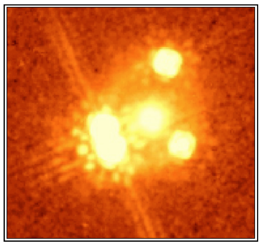 This shows the four images of the quasar PG 1115+080 surrounding the galaxy that causes the light to be lensed.