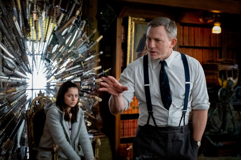 Actress Ana de Armas sitting in a knife chair, and Daniel Craig wearing a suit speaking with his hand out.