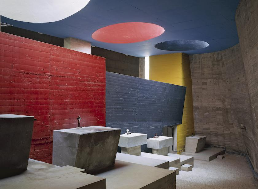 Large circular light shafts painted in cherry red and deep grey relate to the color-blocked walls in the crypt of La Tourette