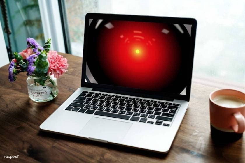 A laptop on a home desk, its screen filled with the red eye of HAL9000 from 2001: A Space Odyssey.
