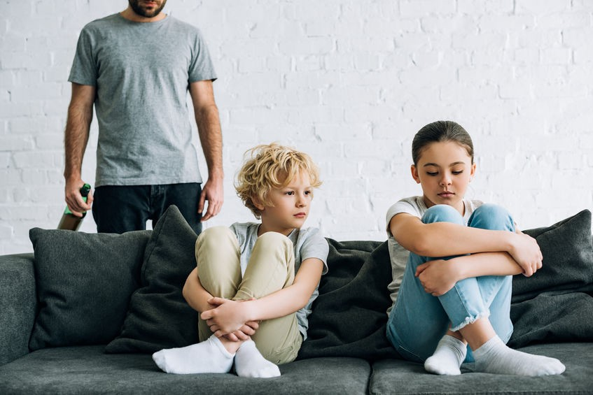 kids on couch with adult male in background
