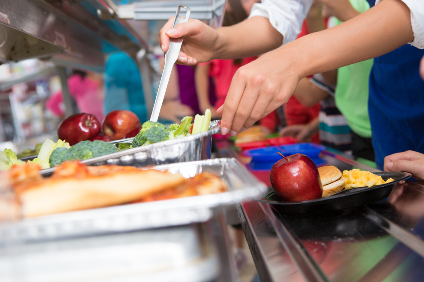 A school lunch scene with a cafeteria worker scooping broccoli for a lunch tray.