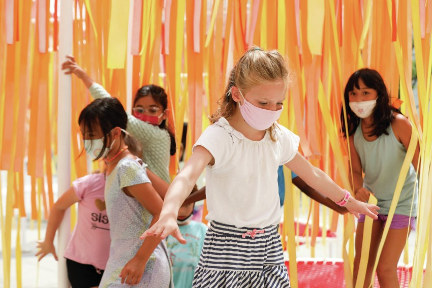 A group of young girls wearing masks play outdoors under a sea of hanging yellow and orange strips.