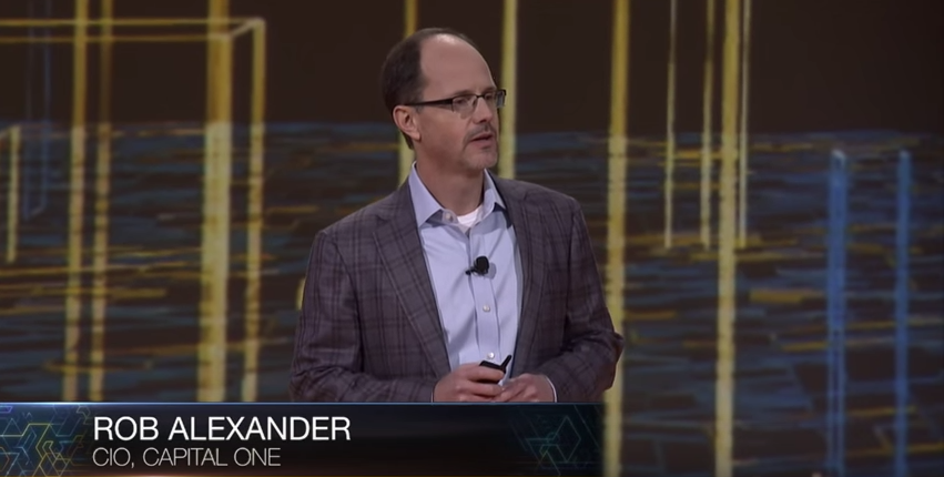 Rob Alexander in a blazer and blue button up shirt presenting on a stage.
