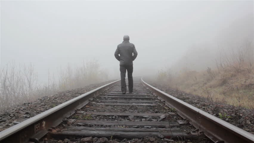 A man dressed in black is seen walking away from the camera, onto a rail track disappearing in the fog…