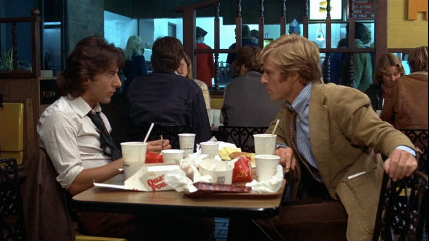Still from the movie All the President's Men. Two men looking at each other across a table in a fast food restaurant.