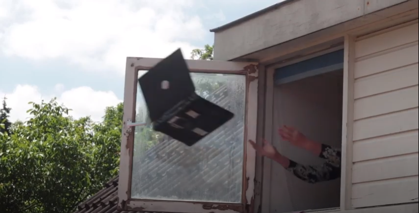 Guy throwing a laptop out the window