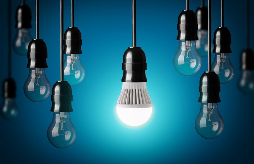 A lit LED bulb shines amidst unlit simple light bulbs, hanging at different lengths, against a blue background.
