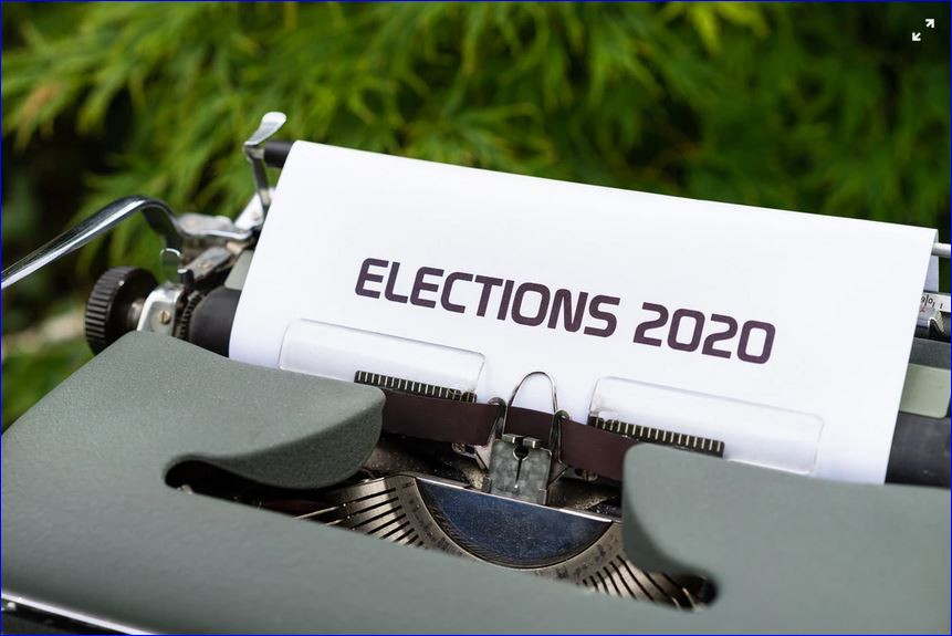 """An antique typewriter with a page reading """"Elections 2020"""" sits on a desk outside with plants in the background."""
