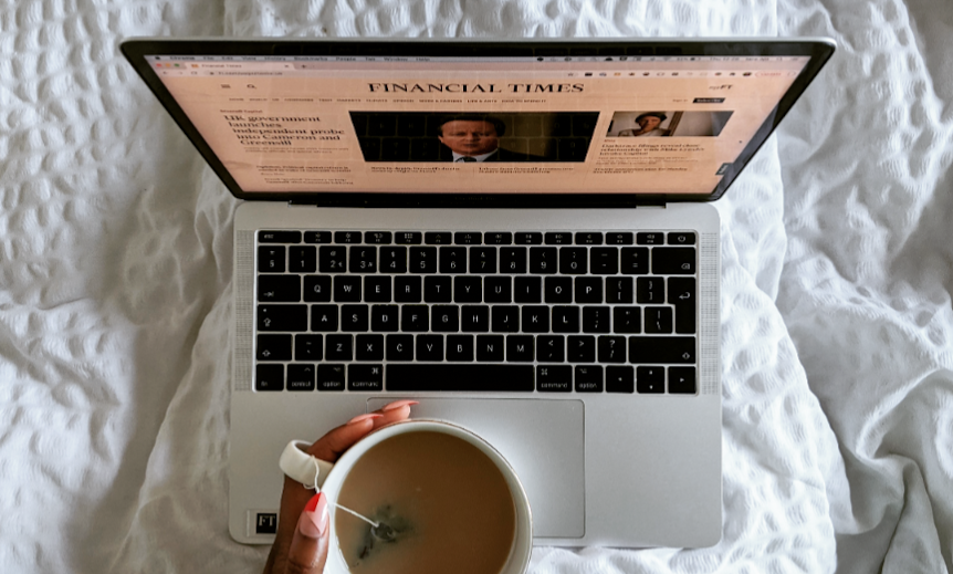 Laptop showing the Financial Times homepage on a bed with a cup of tea in hand and funky red and pink nails
