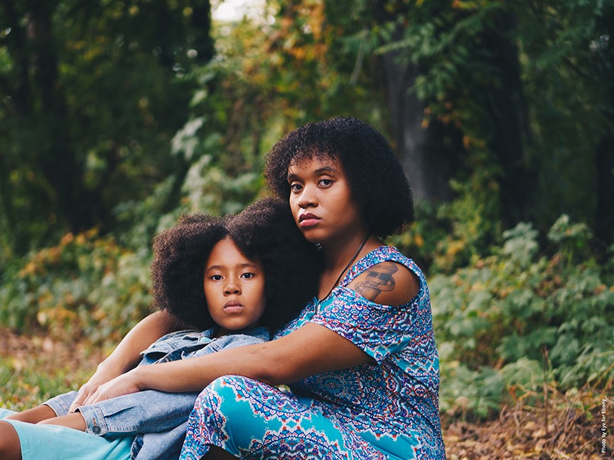 Concerned young mother and daughter sitting together in an outdoor setting. Photo by Eye for Ebony.