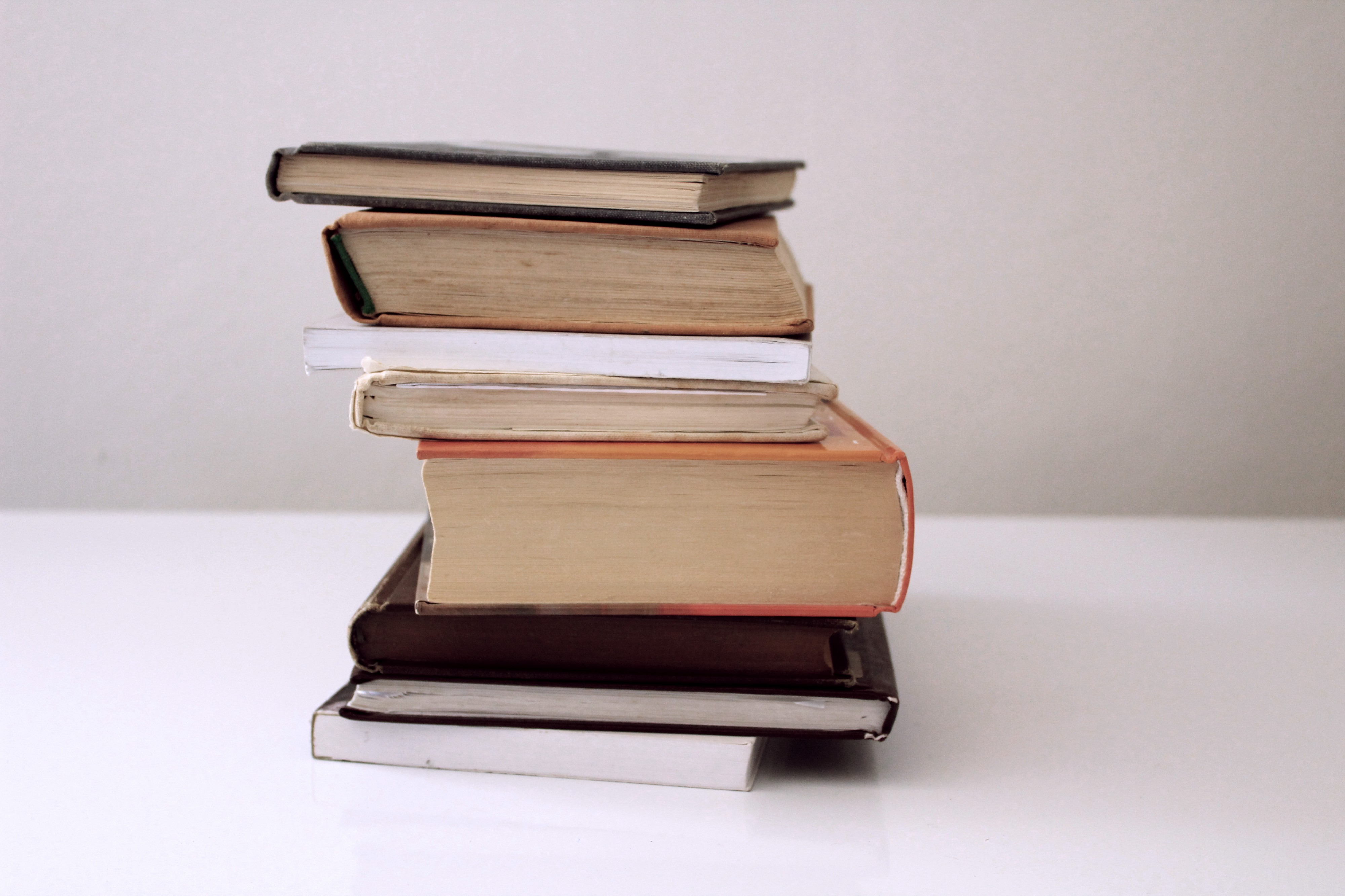 Stack of old books on an empty table with a blank backdrop