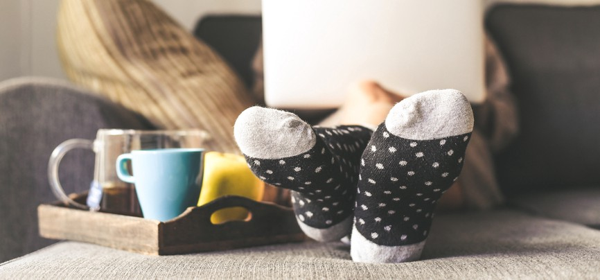 Socked feet on an ottoman next to mug and bowl in the foreground, laptop on lap covering face blurred in the background.