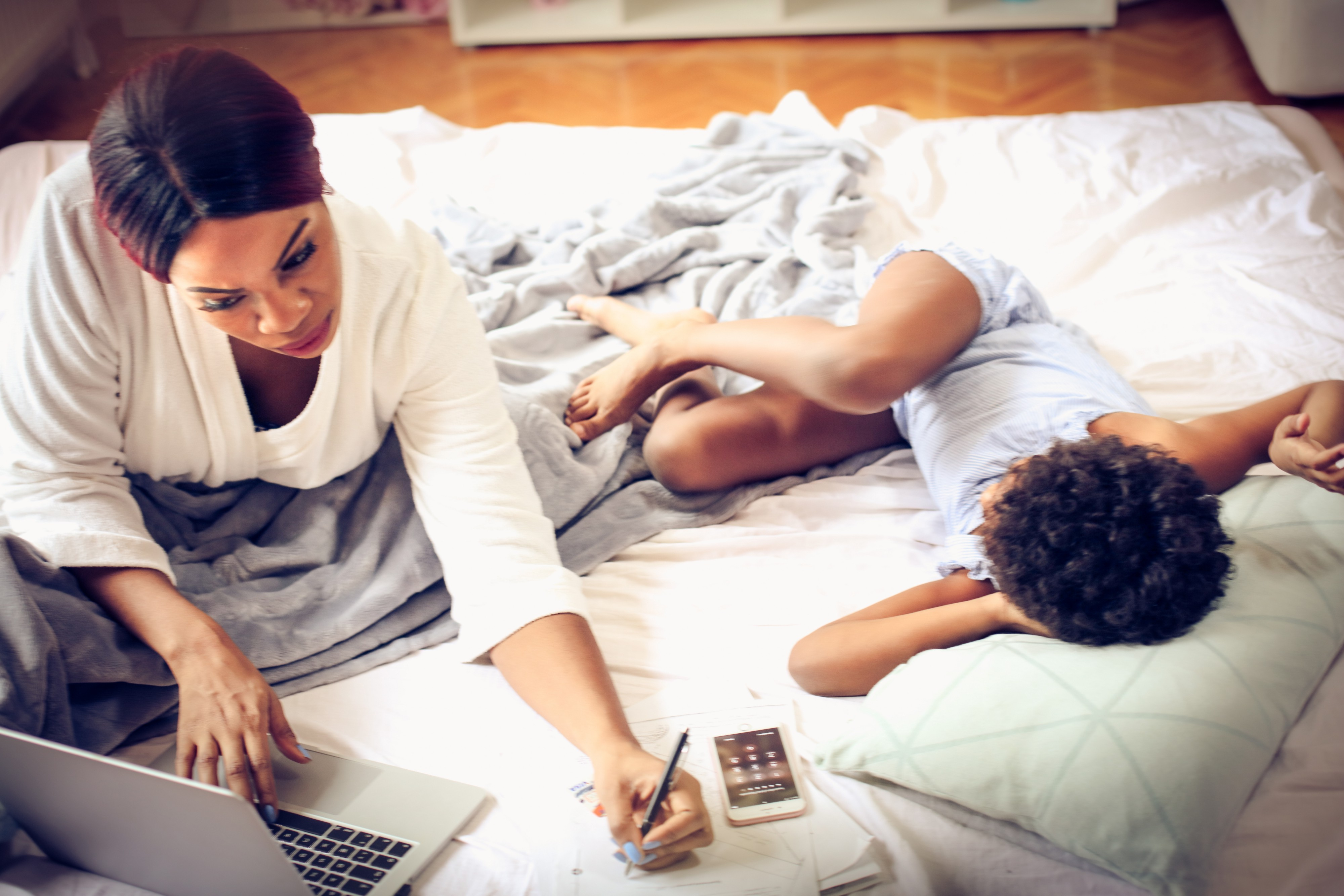 A woman looks at her laptop, working on her bed with her young daughter beside her.