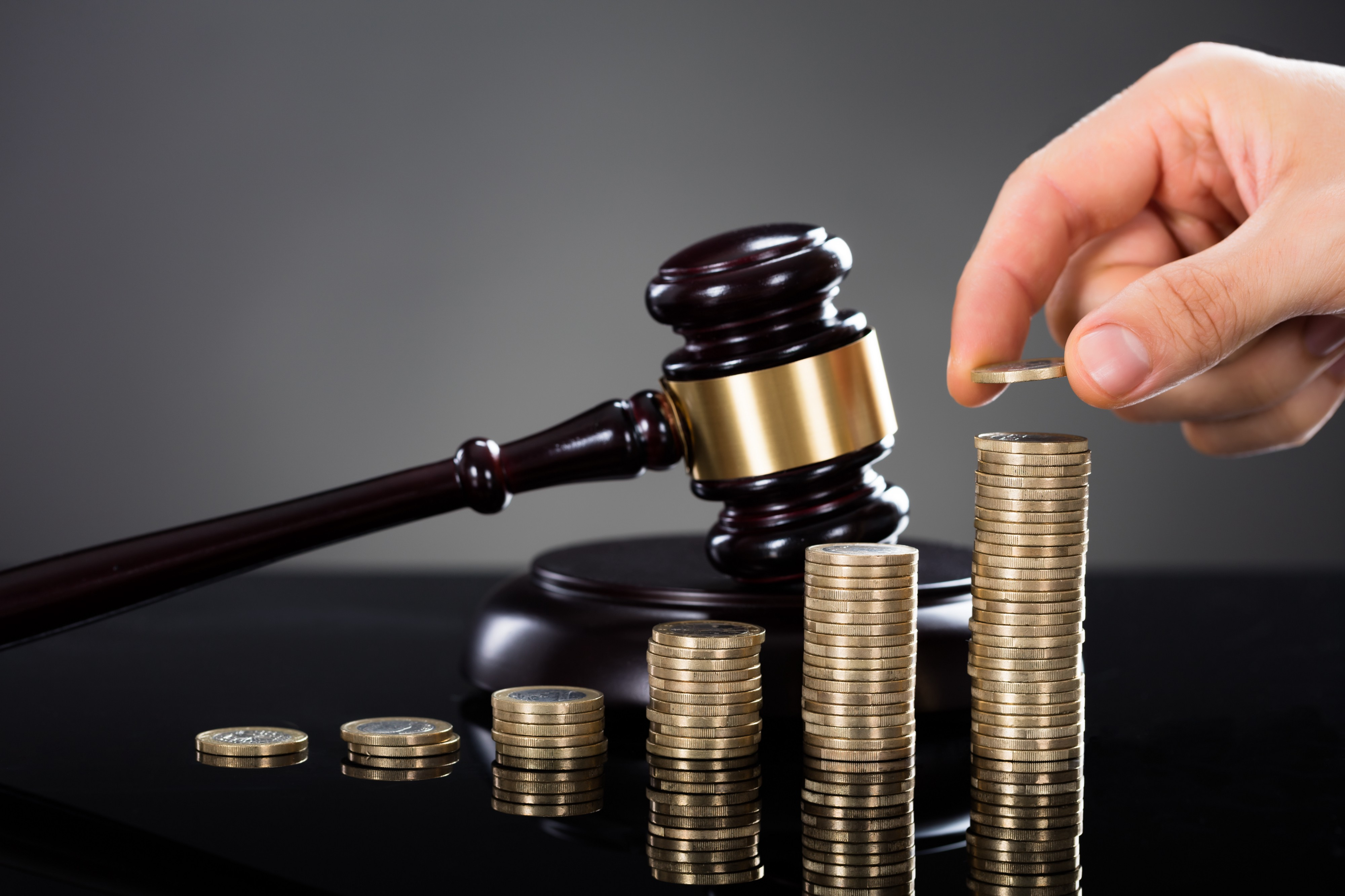 Gavel next to six stack of coins of increasing heights with a hand placing a coin on the top of the highest stack