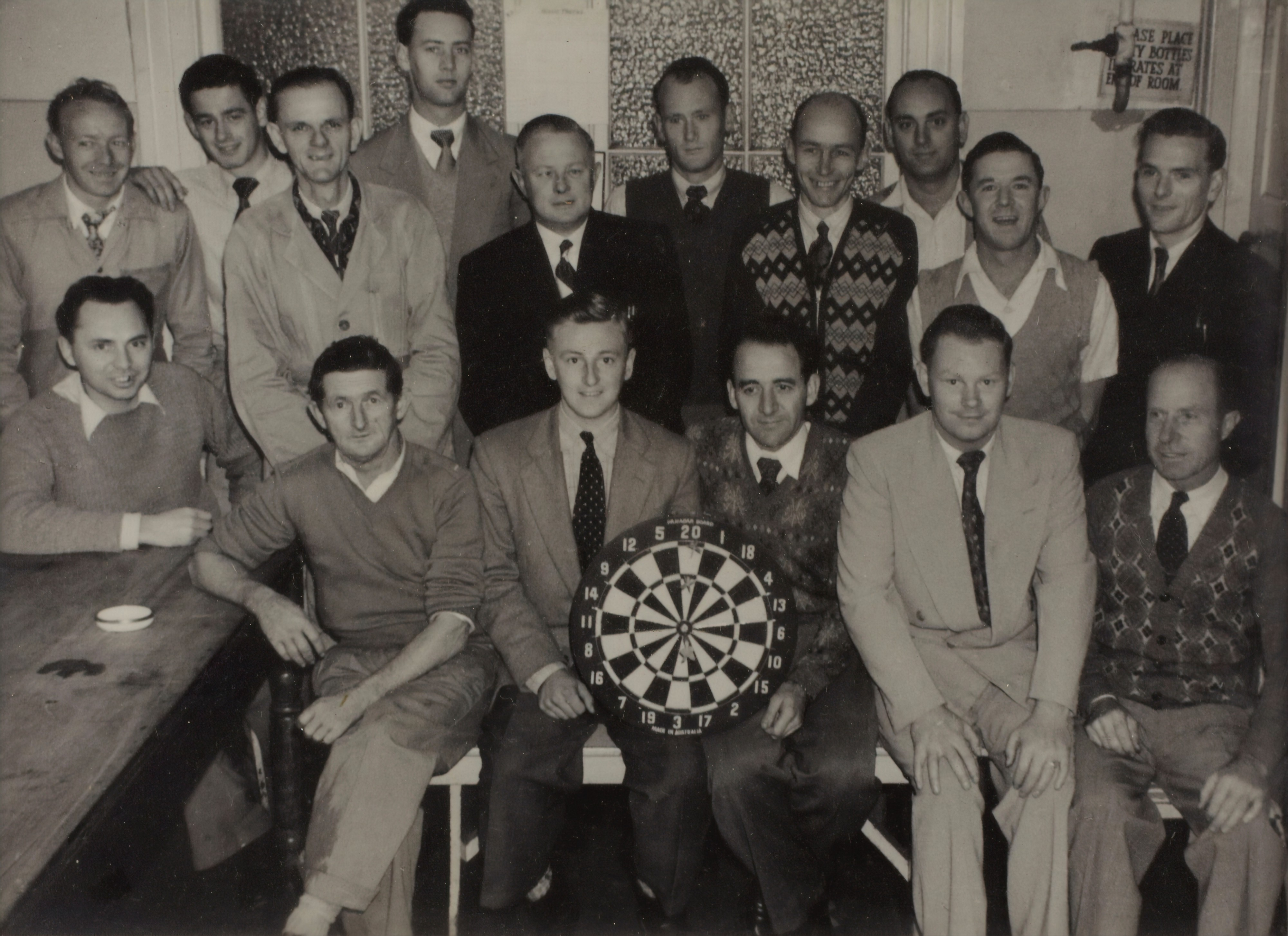 group of caucasian men in group photo holding a dart board