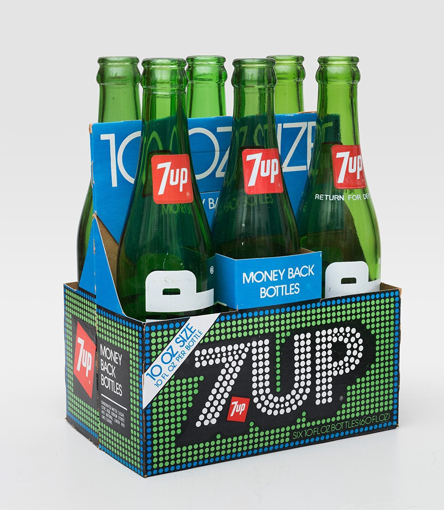 """Image of Thomas Miller's 7up design. Six green glass bottles in a green box with green, blue and white polka dot design. 7up is written in white bold typeface with a polka dot design. The green bottles have a red label with 7up written in white. There is a blue sign on the central bottle that says """"money back bottles."""""""