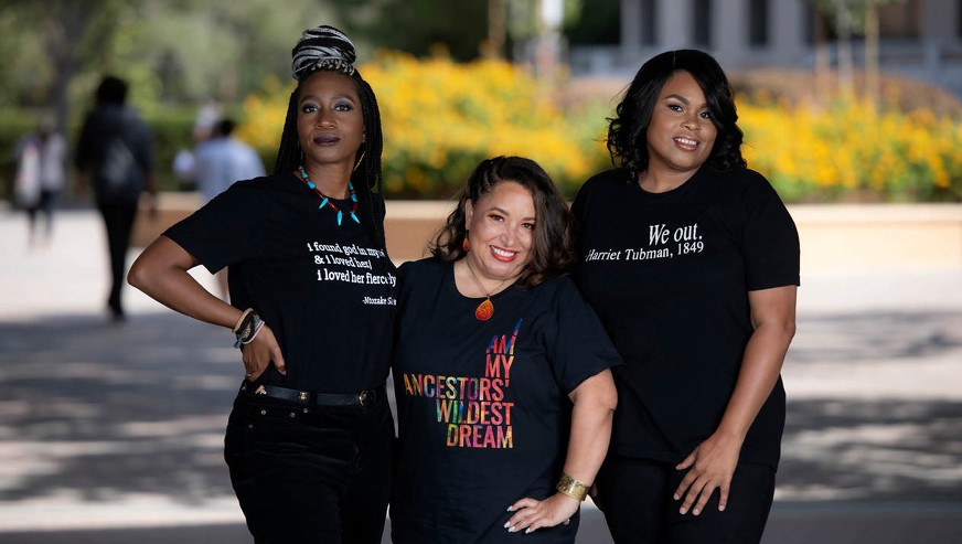 Tiffany Willoughby-Herard, Jessica Millward, and LaShonda R. Carter stand in a line together smiling