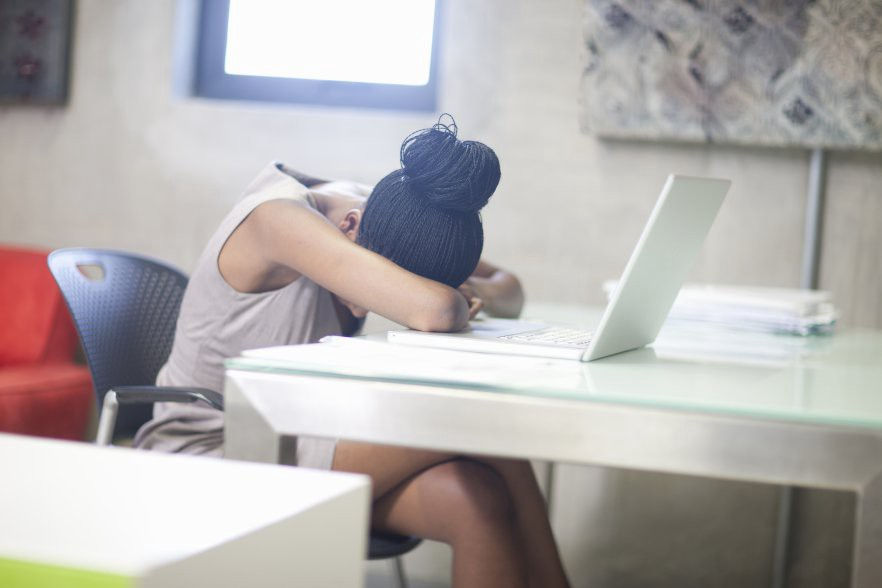 A photo of a person at a desk with their head down in front of a laptop