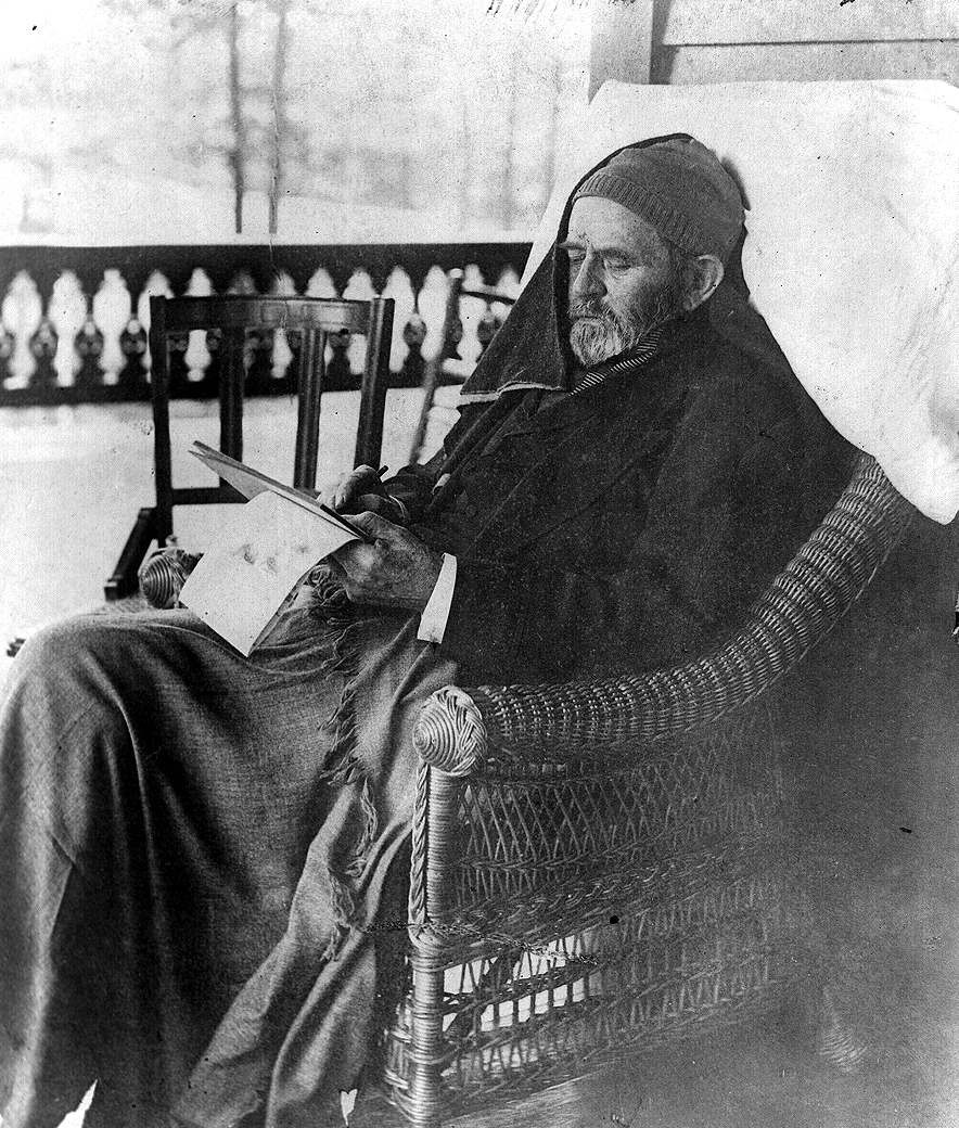 Ulysses Grant, three-quarter length portrait, seated in rattan chair, writing memoirs, at Mount McGregor, New York.