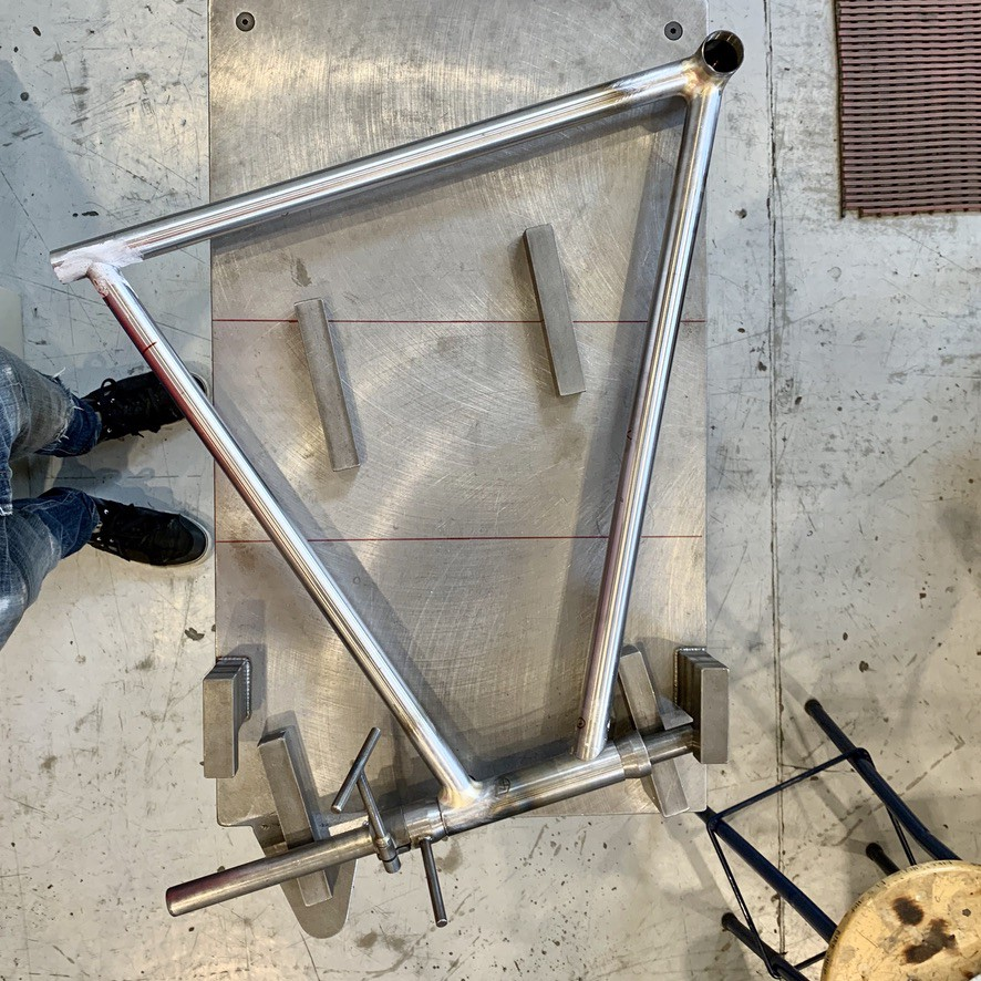 A bicycle frame resting on an alignment table