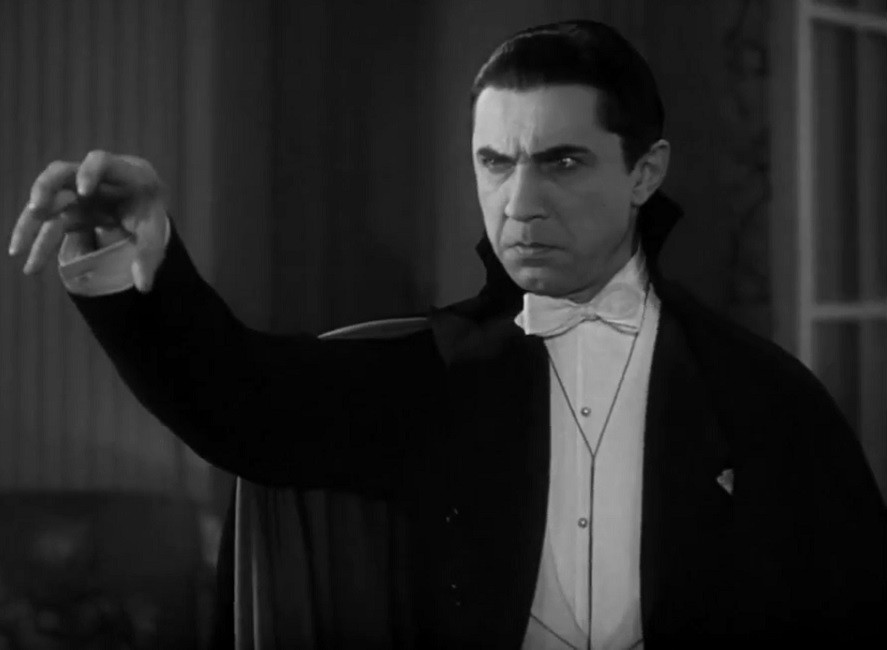 Film still of Bela Lugosi as Dracula with intense gaze and outstreched hand in claw gesture.