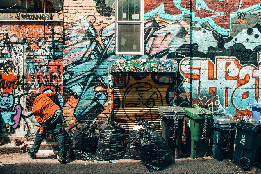 A person leaning into a wall near some bins and rubbish bags