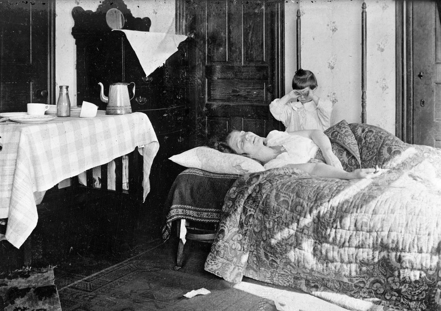 A girl stands next to her sister, who is lying in bed, in November of 1918. The young girl became so worried that she telepho