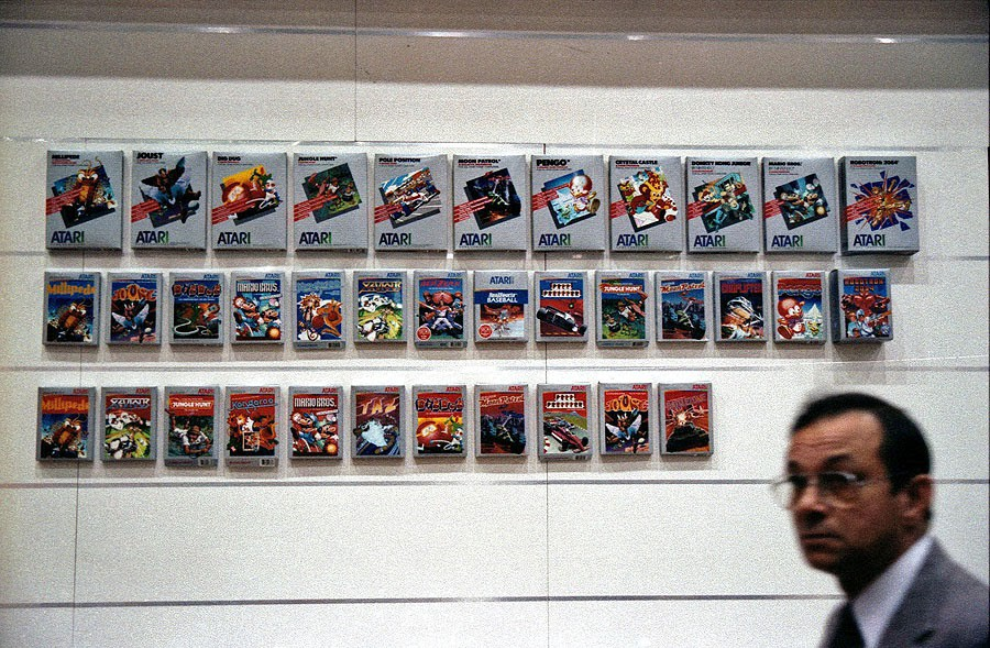 Atari 2600 game boxes displayed on a wall at a CES Expo.