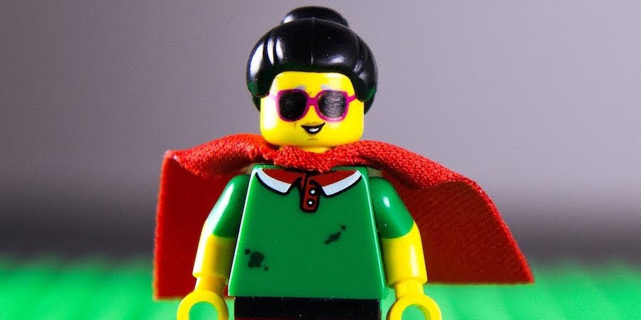 A Lego figurine with visual impairments who is wearing a red cape stands upright.