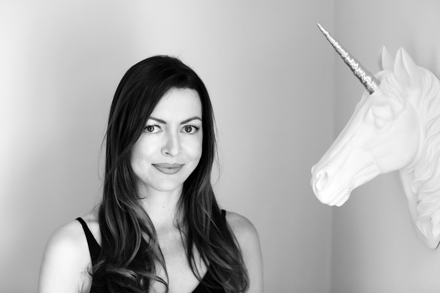 A black and white photo of Jo, smiling next to a unicorn wall hanging