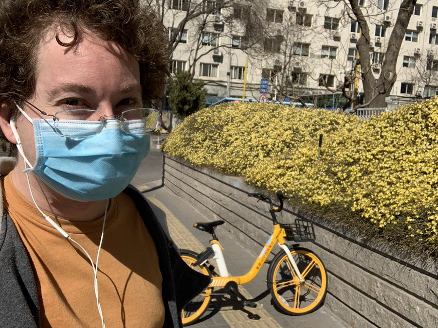 The author stands in front of a bush of yellow blossoms and a yellow bicycle. They are wearing a medical mask.