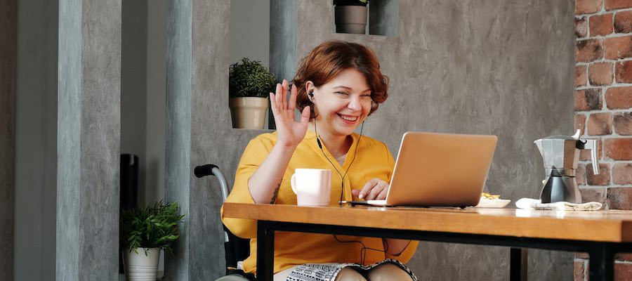 Lady waving during video chat session on her laptop