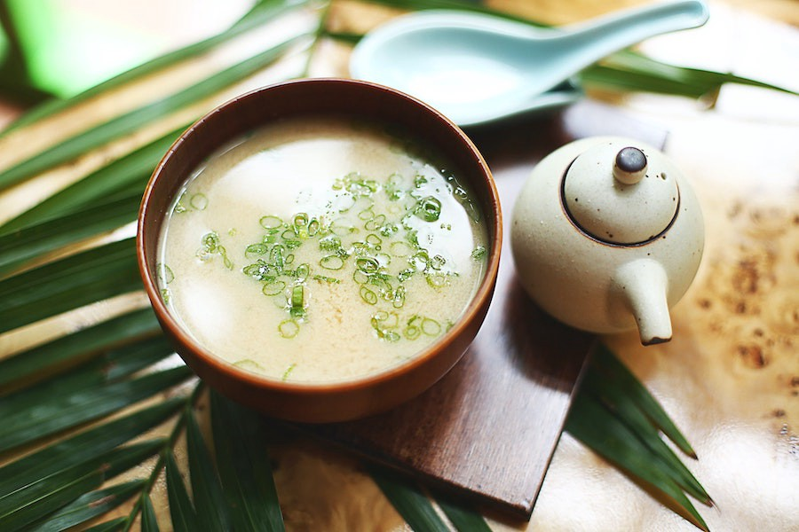 A bowl of miso sits beside a pot of tea.