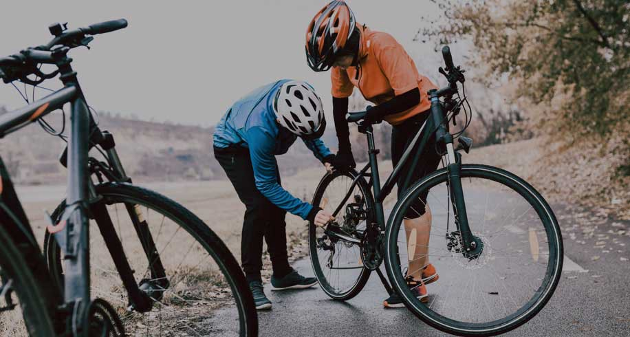 Two cyclists checking their bicycle hub while on an outdoor ride.