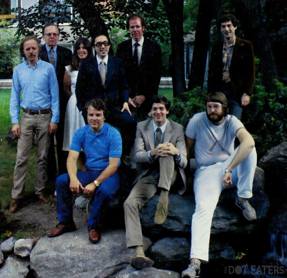 The picture shows a staff photo of the Infocom employees in 1982 awkwardly posing for the camera while sitting on a rock.