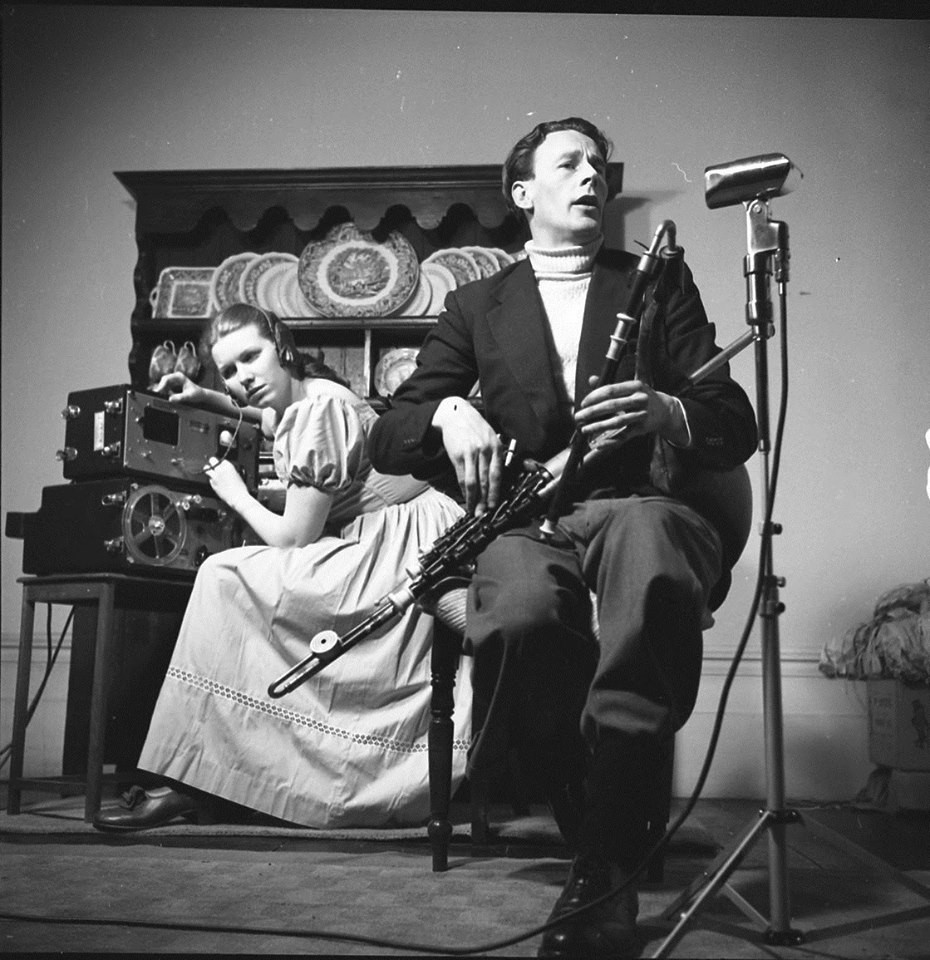 In the foreground, Séamus Ennis sits with his pipes. In the background, Jean Ritchie is leaning intently over her recording equipment.