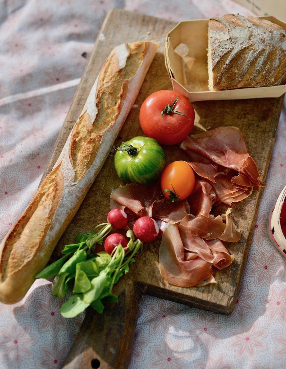 Charcuterie board picnic with french bread, tomatoes, and cured meats.
