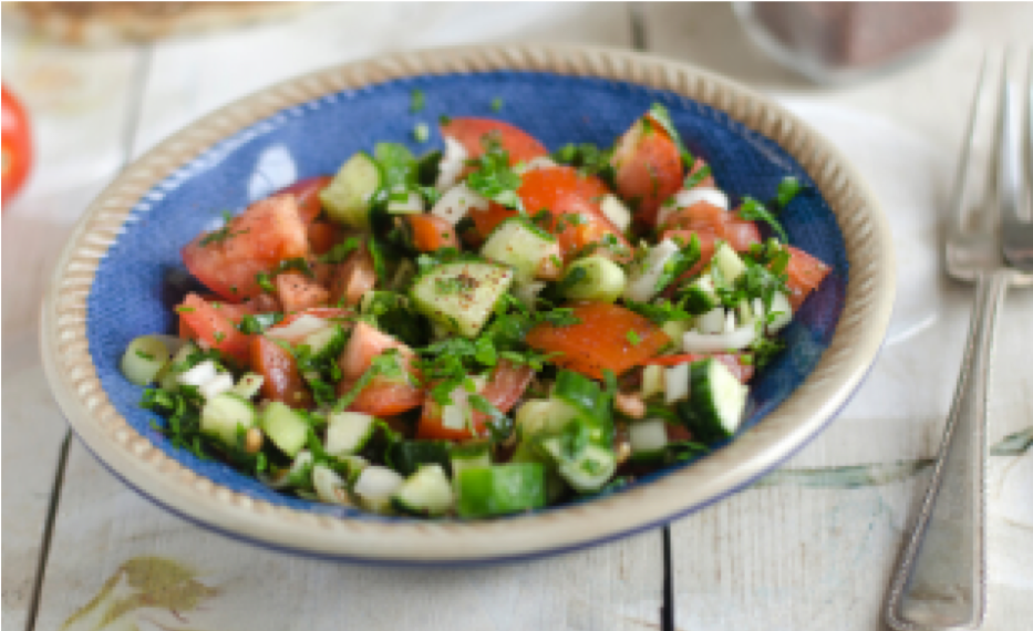 Blue plate full of cucumber and tomato salad.