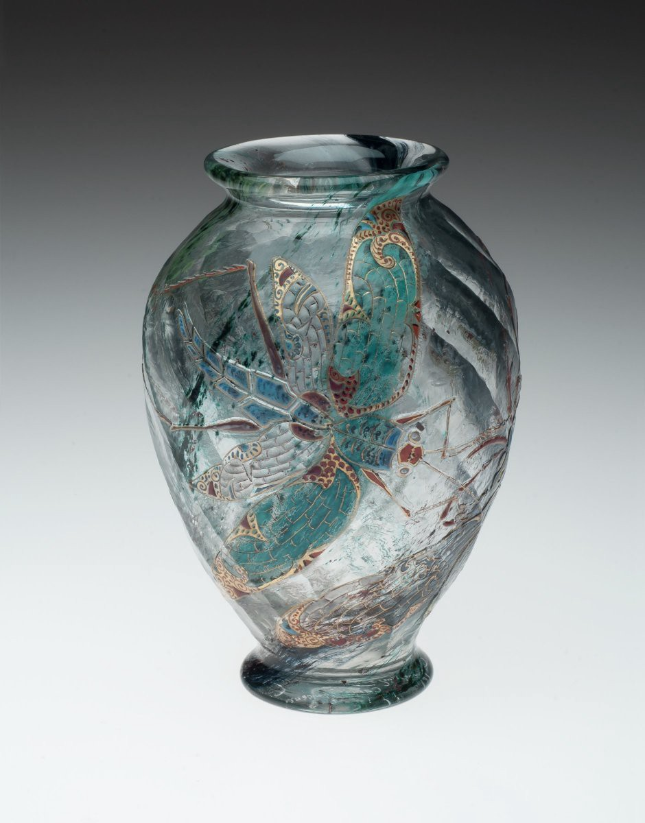 Glass vase with a dragonfly design in green and gold.