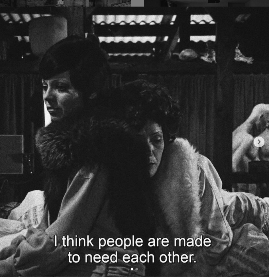 Screenshot of The Bitter Tears of Petra von Kant (1972) Rainer Werner Fassbinder. Two women dressed in furs lean against eat other, one appears to be sleeping. The subtitle reads: I think people are made to need each other.