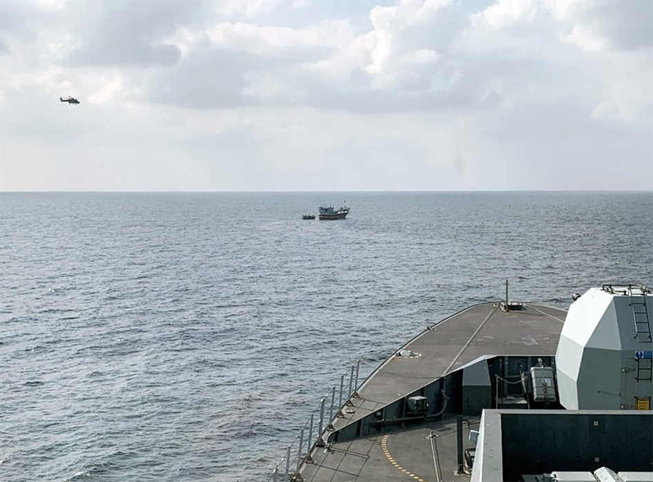 An image of a Wildcat helicopter flying towards an unidentified dhow vessel with HMS Defender in the bottom of the shot