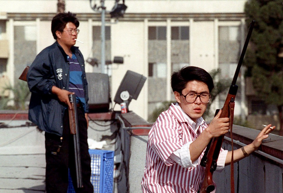 Two armed Korean business-owners protecting their store from the rooftops during the LA Riots.