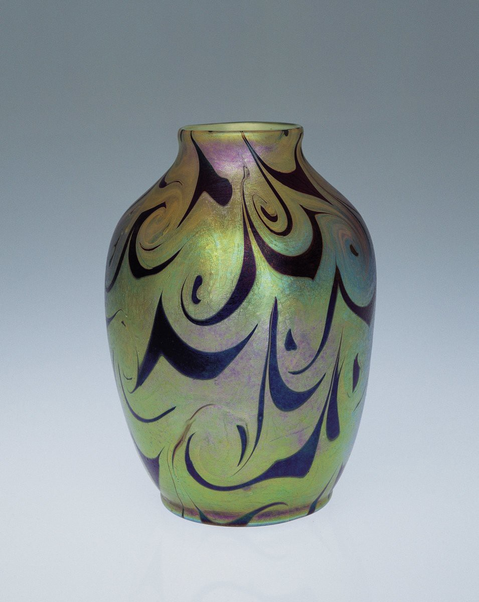 Glass vase with black designs on a green, purple, and blue iridescent background.