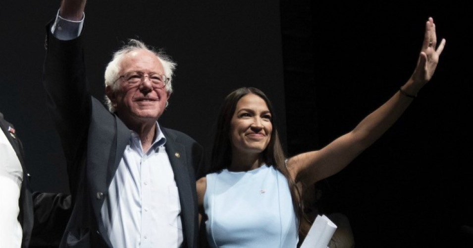 Bernie Sanders and Alexandria Ocasio-Cortez with one arm around each other and the other arm waving to voters.