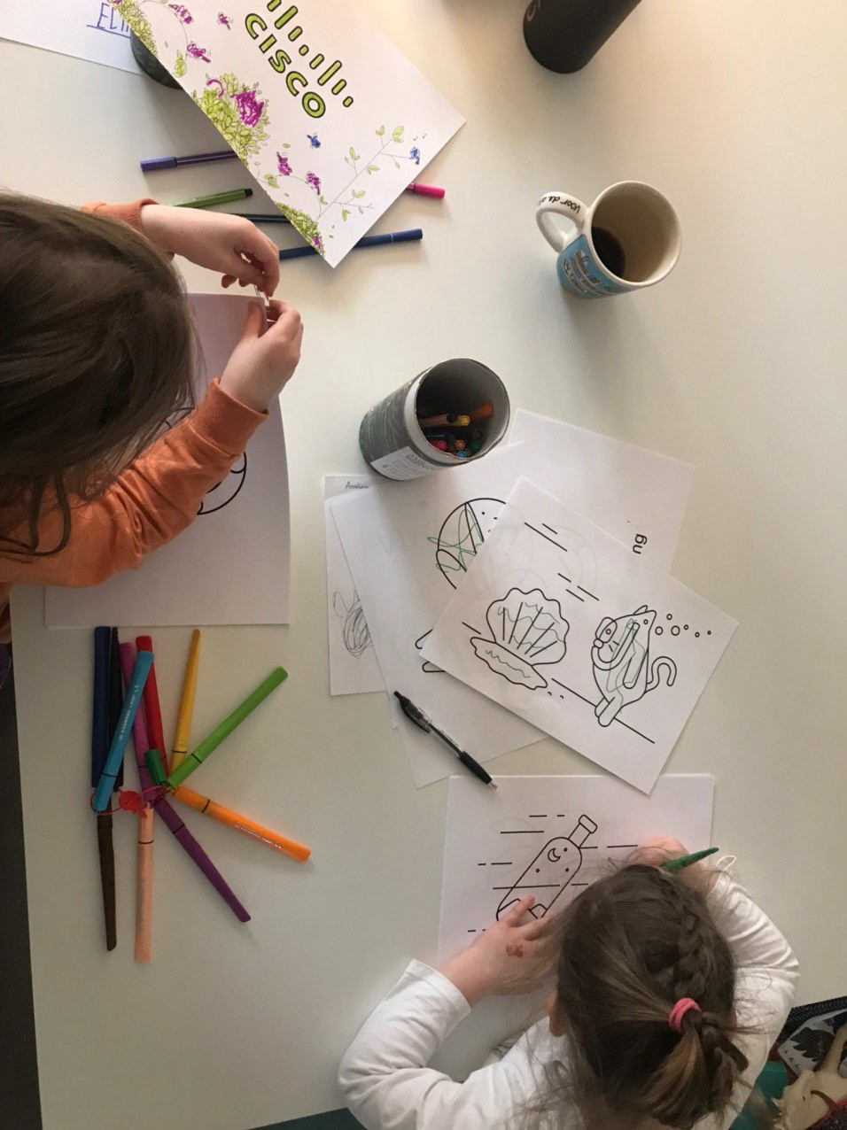 An overhead view of two children colouring in their pages
